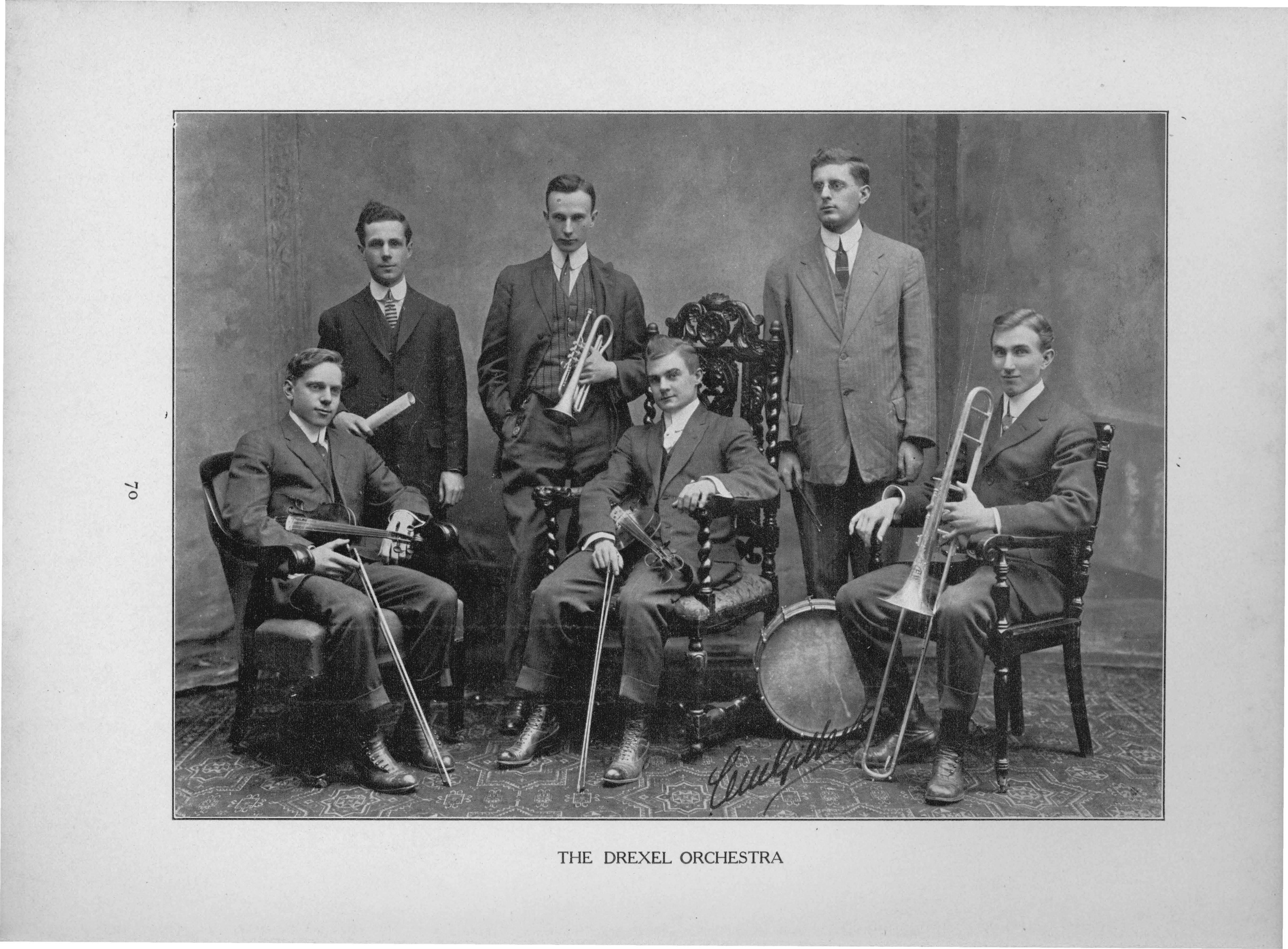 Six men stand in a semi-circle holding a variety of instruments