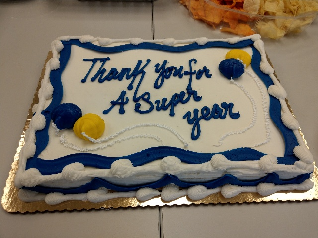 A cake with white icing and blue trip with yellow ballons. The cake says 'Thank you for a super year.'