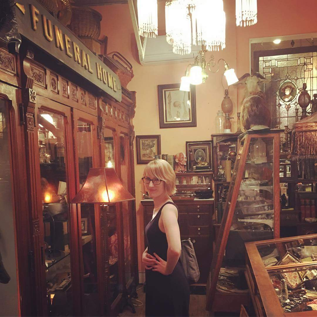 A woman stands next to a large wooden display case filled with antiques.
