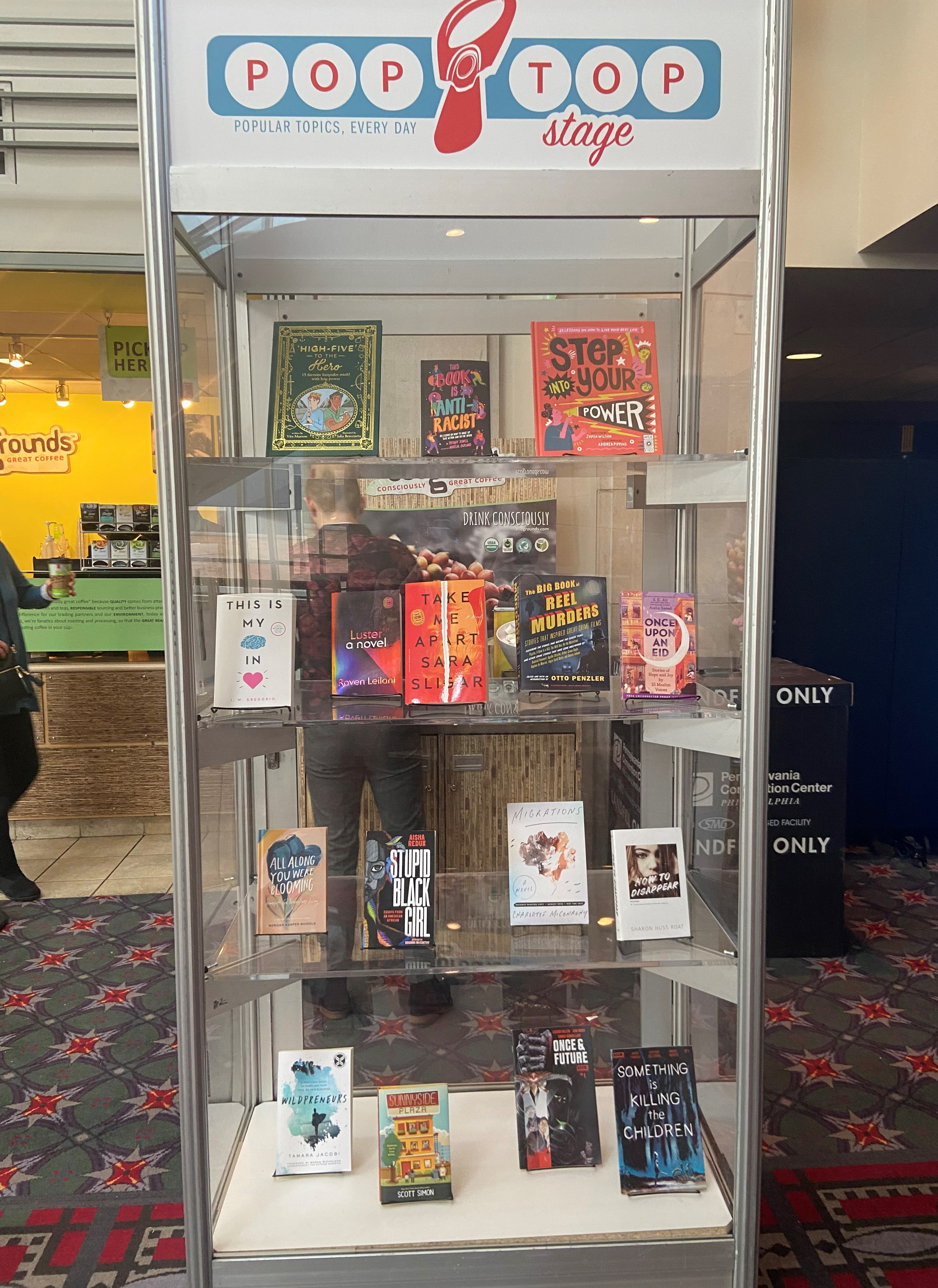 A display case with books on each shelf