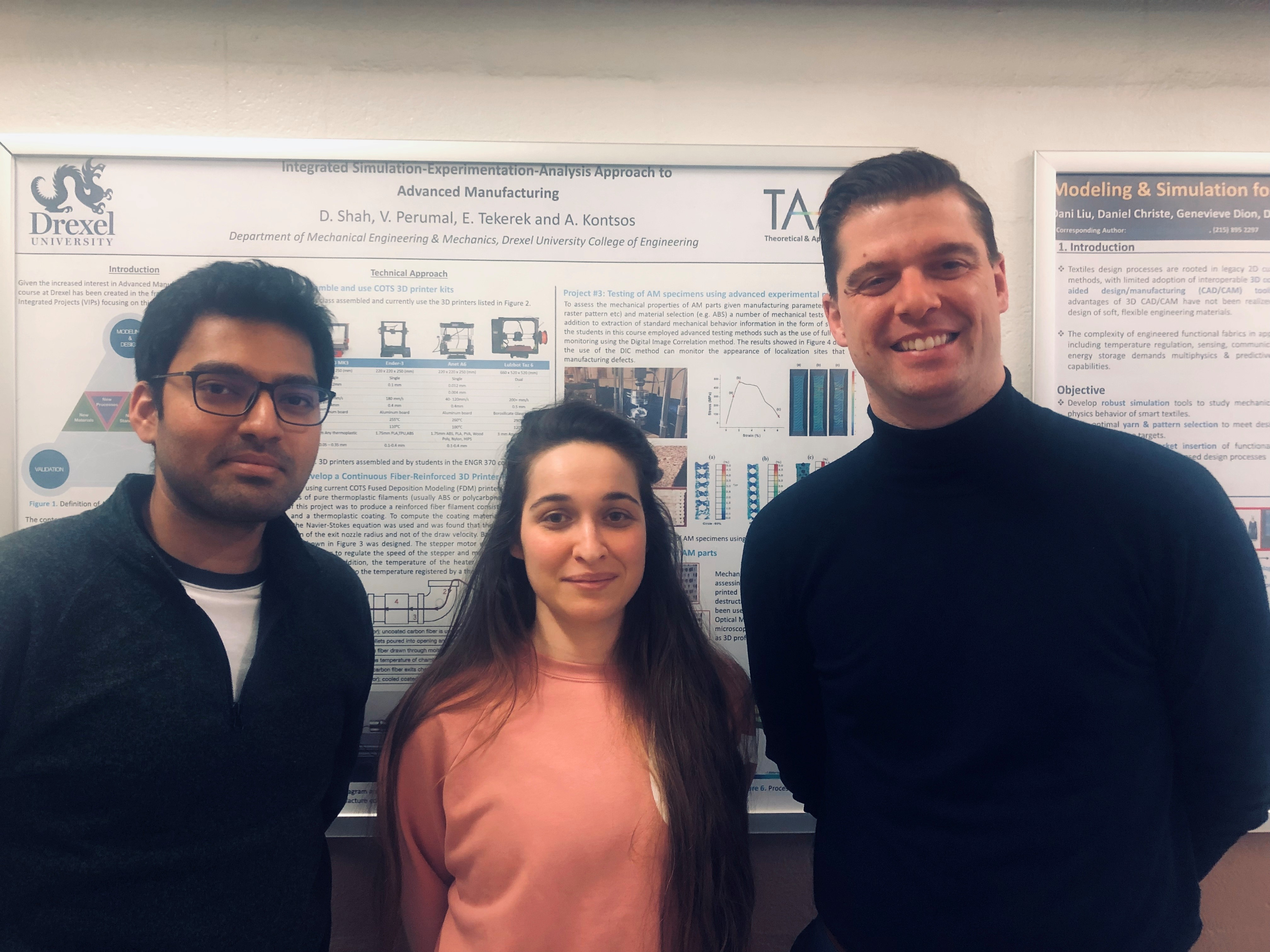 Two men and one woman stand in front of an engineering poster