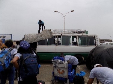 Drexel students, faculty and staff wearing backpacks stand in a parking lot in Senegal while a man covers a buss with a tarp.