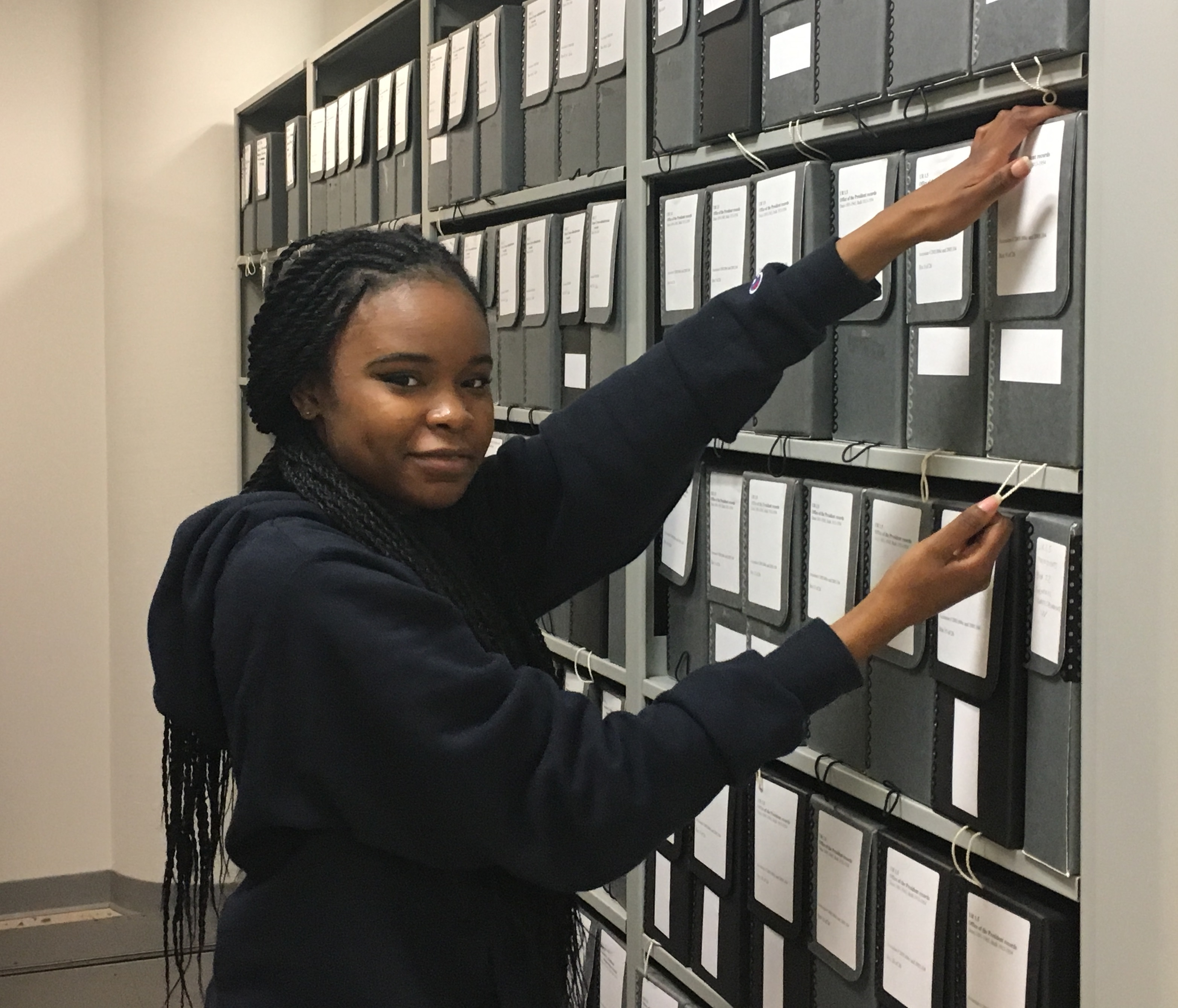 A young woman poses in front of shelves lined with folders of archival materials