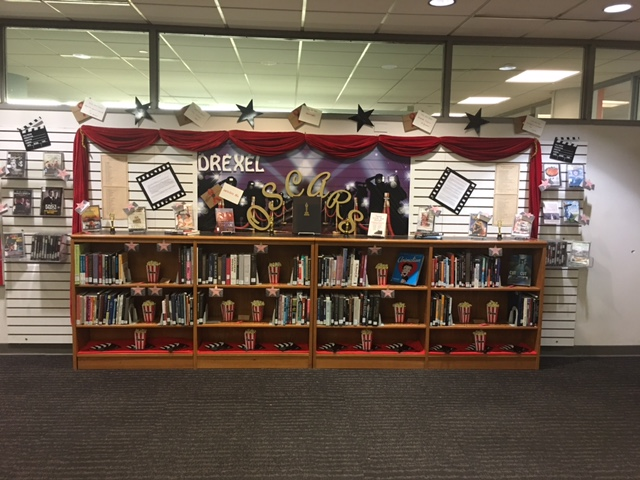 Bookshelves are filled with books and movies. All books and movies on display are past Oscar winners and nominees.