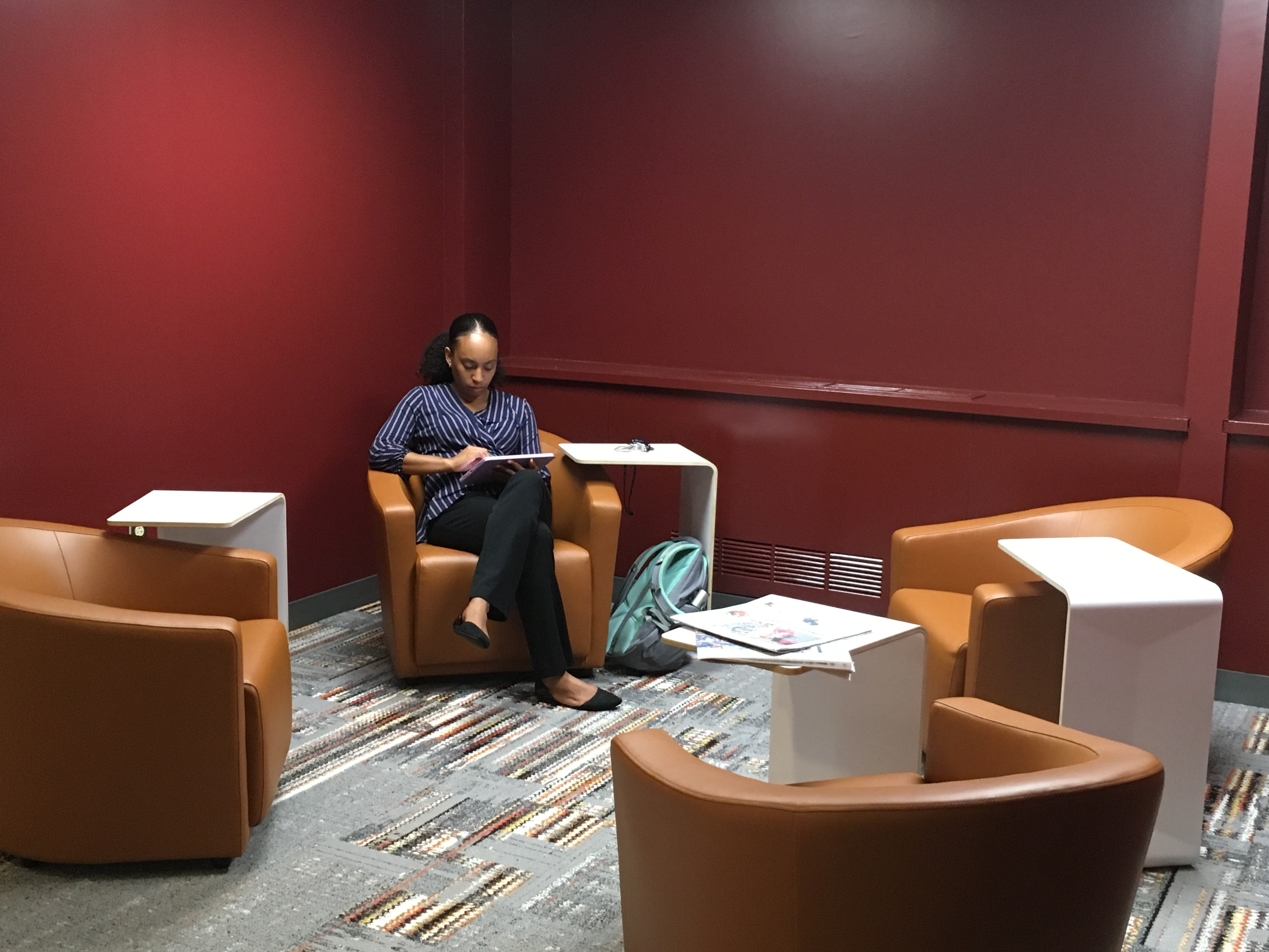 A women sits in a chair in the Queen Lane Library lobby