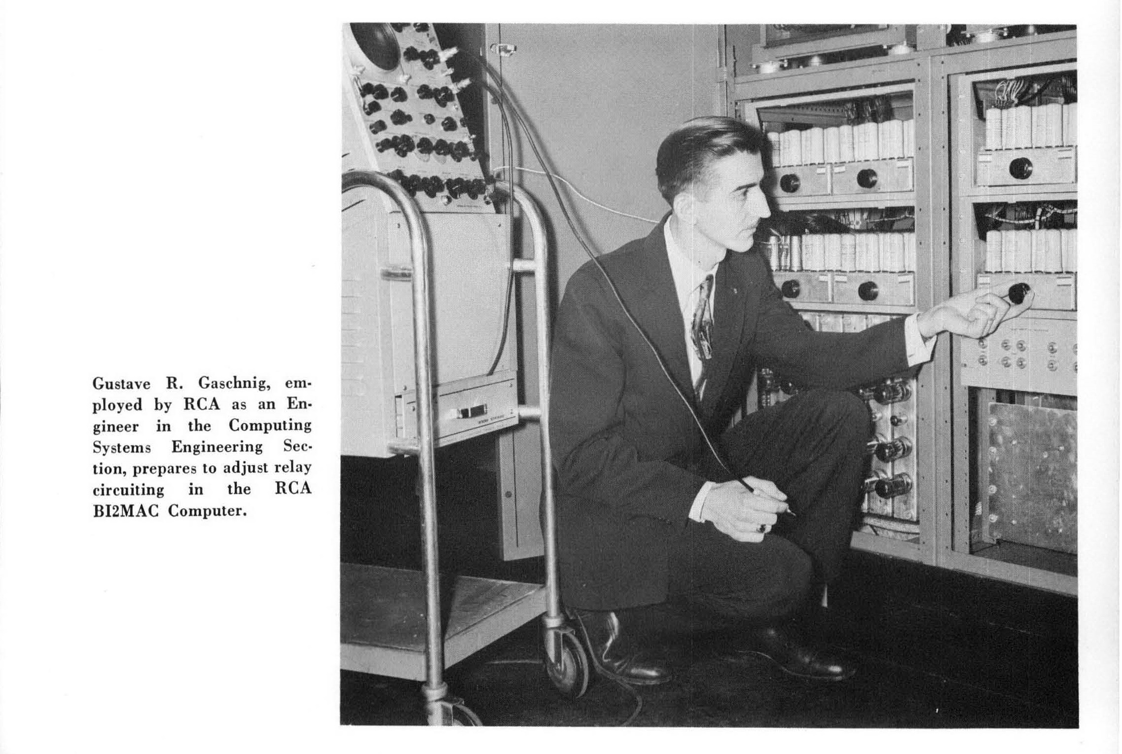 A man kneels beside a computer from the 1950s