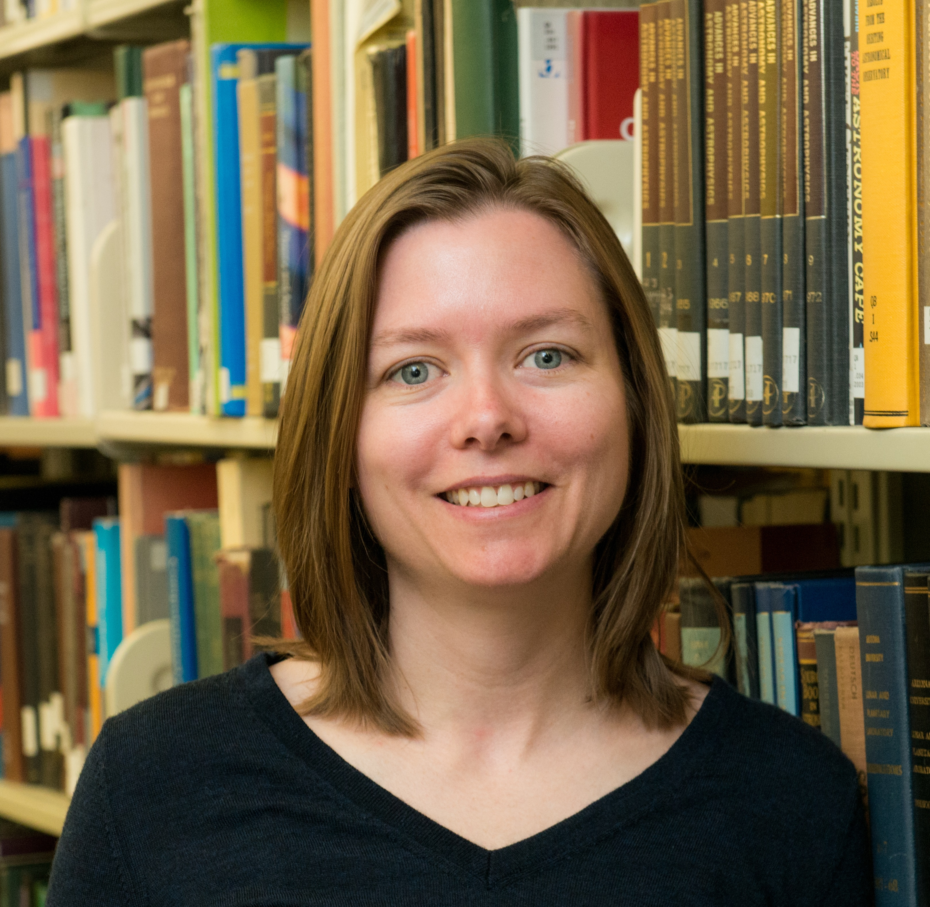 A headshot of a woman standing on the 2nd floor of the Hagerty Library