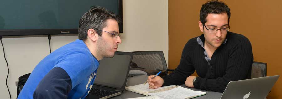 Two students collaborating on an assignment in a library study room.