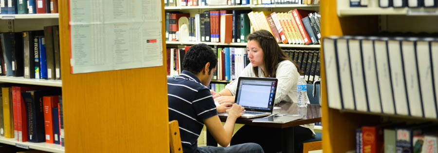 Two students working on a project together in the library stacks.